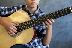 Teenage boy playing his  guitar Stock Photo