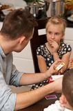 Teenage boy playing card game with his sister. A teenage boy sitting at a kitchen table, playing a card trivia game with his younger sister. Family leisure time Stock Photos