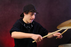 Teenage boy playing drums Stock Images
