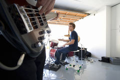 Teenage boy (16-18) playing drums in garage, looking at friend playing electric guitar in foreground Royalty Free Stock Image