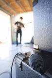 Teenage boy (16-18) playing electric guitar in garage, focus on microphone in foreground Royalty Free Stock Photos