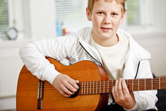 Teenage boy playing guitar Stock Images