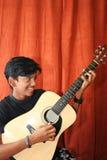Teenage boy playing guitar. Happy teenage boy playing guitar Royalty Free Stock Images