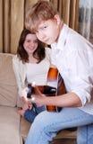 Teenage boy playing by guitar Stock Photos