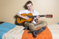 Teenage boy playing guitar in her bedroom stock photo
