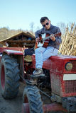 Teenage boy playing guitar on a tractor Royalty Free Stock Photos