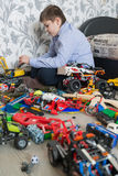 Teenage boy playing with toy cars in  room. Teenage boy playing with toy cars in the room Stock Photography