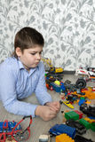 Teenage boy playing with toy cars in  room. Teenage boy playing with toy cars in the room Stock Photos