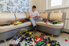 Teenage boy playing with toy cars in  room. Teenage boy playing with toy cars in the room Royalty Free Stock Photo