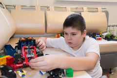 Teenage boy playing with toy cars in  room. Teenage boy playing with toy cars in the room Royalty Free Stock Photography