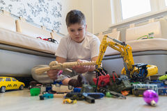 Teenage boy playing with toy cars in  room. Teenage boy playing with toy cars in the room Royalty Free Stock Images