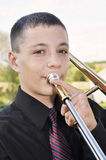 Teenage boy playing trombone Royalty Free Stock Image