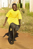 Teenage Boy Playing with Tyre - Yellow T-Shirt. Young teenage boy, wearing a bright yellow t-shirt, playing with the tyre of a 24 inch bicycle Royalty Free Stock Image