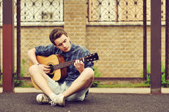 Teenage Boy plays an acoustic guitar. Outdoors Royalty Free Stock Photos