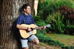 Teenage Boy plays an acoustic guitar Royalty Free Stock Images