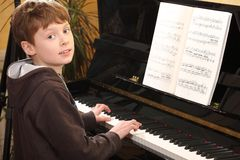 Teenage boy plays piano Stock Images