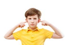 Teenage boy plugs ears Royalty Free Stock Image