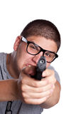 Teenage Boy Pointing a Gun. An angry looking teenager wearing black frame glasses points a black handgun at the viewer. Shallow depth of field with focus on the Stock Photography