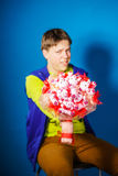 Teenage boy posing with bouquet of flowers Royalty Free Stock Image