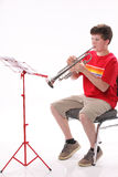 Teenage Boy Practicing Trumpet. A male early teenage boy child playing trumpet facing to the left isolated against a white background with copy space in the Royalty Free Stock Photo