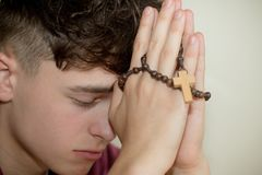 Teenage boy praying. With a rosary stock photos