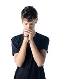Teenage boy praying with rosary Stock Photo