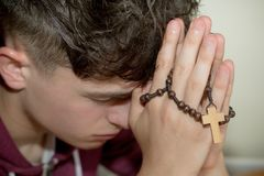 Teenage boy praying. With a rosary royalty free stock image