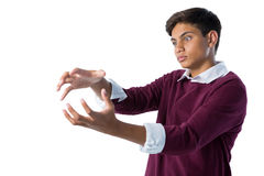 Teenage boy pretending to hold an invisible object. Against white background Stock Photography