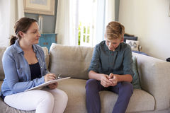 Teenage Boy With Problem Talking With Counselor At Home stock image