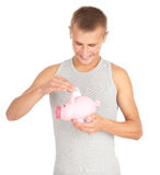 Teenage boy putting five euro in piggy bank Stock Photos