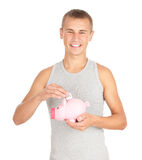 Teenage boy putting five euro in piggy bank Stock Images