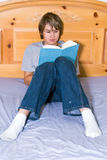 Teenage boy reading in bed Royalty Free Stock Photo