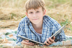Teenage boy reading big book Royalty Free Stock Image