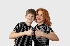 Teenage boy and redhead woman show thumbs up gesture Stock Image