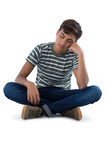 Teenage boy relaxing against white background. Thoughtful teenage boy relaxing against white background Royalty Free Stock Photography