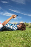 Teenage boy relaxing on phone. Smiling Stock Photo