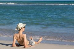 Teenage boy relaxing at the sea shore on sandy beach. And enjoying view to the open sea Royalty Free Stock Image