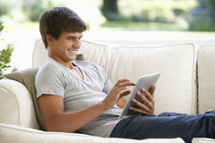 Teenage Boy Relaxing On Sofa At Home Using Digital Tablet Stock Photography