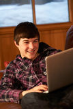 Teenage Boy Relaxing On Sofa With Laptop. In Chalet Royalty Free Stock Photography
