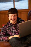 Teenage Boy Relaxing On Sofa With Laptop. In Chalet Stock Photography