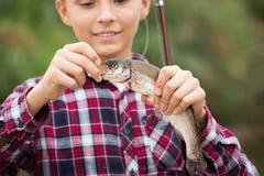 Teenage boy releasing catch on hook fish Stock Photo