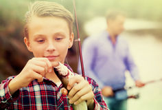 Teenage boy releasing catch on hook fish outdoors Royalty Free Stock Images