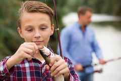 Teenage boy releasing catch on hook fish outdoors Stock Image