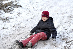 The teenage boy rides from a hill in the snow-covered wood. Royalty Free Stock Photos