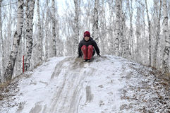 The teenage boy rides from a hill in the snow-covered wood. Stock Images