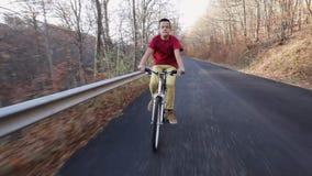 Teenage boy riding his bike on autumn forest road - timelapse. Teenage boy riding his bike on sunny autumn forest road downhill - timelapse stock video