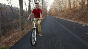 Teenage boy riding his bike on sunny autumn forest road downhill. Enjoying the fall weather outdoors stock video