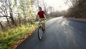 Teenage boy riding his bike on sunny autumn forest road downhill. Enjoying the fall weather outdoors, backlight stock footage