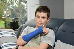 Teenage boy with right arm in plaster stock images