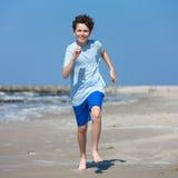 Teenage boy running, jumping on beach Royalty Free Stock Photo